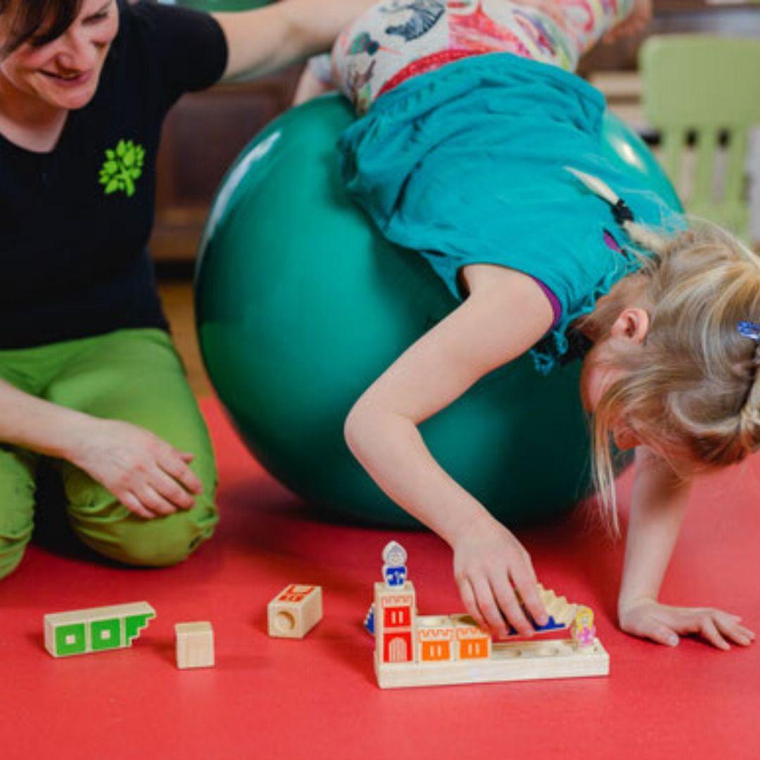 Kinderphysiotherapeutin Verena Schmalz mit Kind auf Pezziball